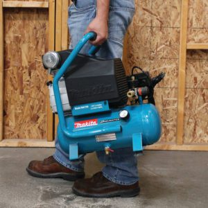 Man Carrying A Small Air Compressor